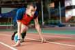 Motivational portrait of determined amputee athlete on start position on running track in modern indoor stadium, copy space
