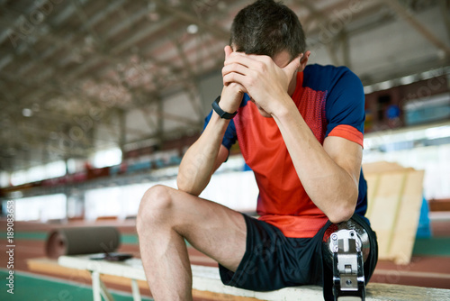 Poster Portrait of young amputee athlete taking break from practice sitting on bench resting head on hands, copy space