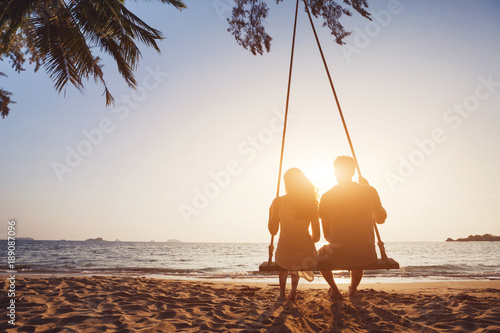 Leinwandbild Motiv romantic couple in love sitting together on rope swing at sunset beach, silhouettes of young man and woman on holidays or honeymoon