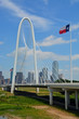 The flag of Texas flys over a highway bridge leading to downtown Dallas.