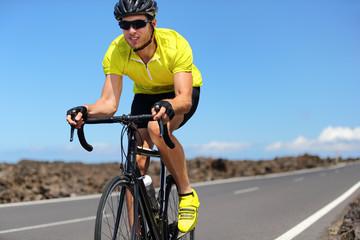 Road bike cyclist man sport athlete training cardio workout on racing bicycle. Male biker biking outdoors training for triathlon.
