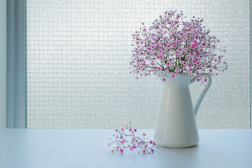 Small pink gypsophila flowers in a white jug on a window background. Soft light from the window. Place for text.