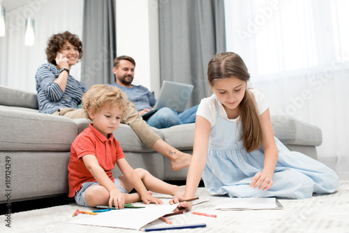 Ordinary day of large family: curly little boy and his elder sister sitting on carpet and drawing pictures with pencils while their pretty mother talking on phone and their bearded dad using laptop