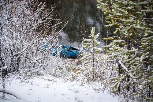 Fotobehang Schip Rubber boat on the river in the winter forest