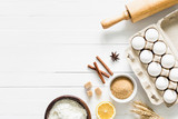 Baking ingredients on white table. White eggs, rolling pin, flour, sugar and spices. Home baking concept, baking cake or cookies ingredients - 189126867