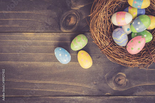 Colorful easter eggs in neat on plank wooden background with space. - 189127432