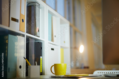 Yellow mug on desk and rows of folders with documents on shelves of office cabinet by workplace of accountant