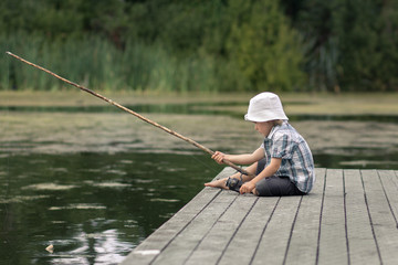 Little boy sitting on a river shore with old-fashioned fishing rod