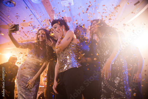 Group  of beautiful young women wearing glittering dresses dancing under golden confetti and taking selfies enjoying raving party in nightclub - 189134251