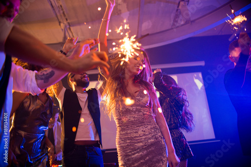 Group of trendy young people celebrating holiday in nightclub burning flaming sparklers in middle of dance floor, focus on dancing beautiful girl wearing glittering velvet party dress