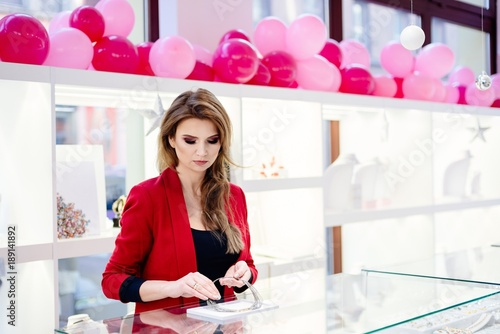 Female seller in a luxury jewelry store presents a necklace. © antic