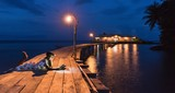 Woman reading book on a wooden warf at night .