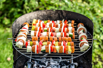 Grilling food on barbecue grill, skewers with vegetables and sausage, grilled food, outdoor bbq in the summer garden