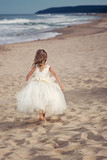 Walk on the beach / Beautiful little girl in a white dress on the background of the sandy beach of the Black Sea
