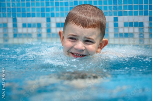 Happy kid playing in pool