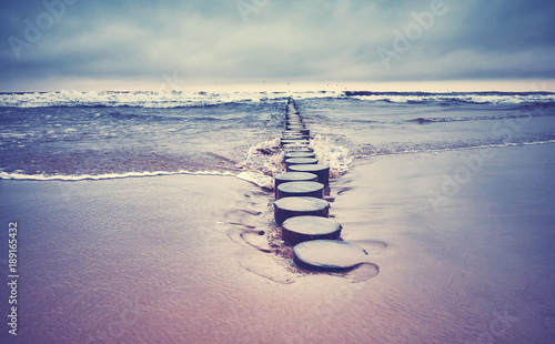Vintage toned picture of an old wooden groyne on a beach, peaceful natural background, selective focus.