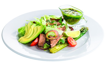 Delicious green meat salad with roasted juicy steak, avocado and green sauce in a white plate isolated on white background
