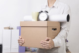 businessman holding personal items box ready moving leaving company. concept layoffs.
