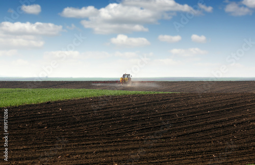 Fotobehang Trekker tractor spraying plowed field at spring