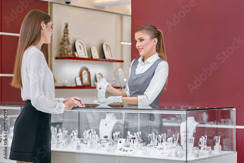 Beautiful female worker wearing white blouse and a grey uniform is showing a necklace with a red stone to a smartly dressed woman near the counter of a fashionable modern jewelry store. © serhiibobyk