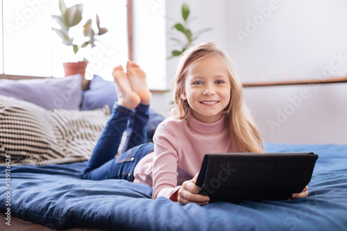 I feel happy. Beautiful inspired fair-haired girl smiling and using her tablet while lying on the bed