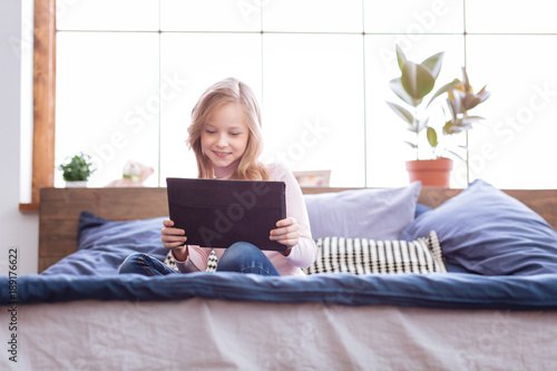 Weekend. Pretty gleeful fair-haired girl smiling and playing games on her tablet while sitting on the bed