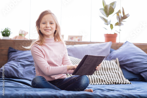 Tablet. Nice glad fair-haired girl smiling and holding her tablet while sitting on the bed