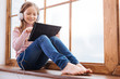 Music. Beautiful inspired fair-haired girl smiling and using her tablet and wearing headphones while listening to music