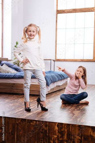 Being an adult. Sweet content fair-haired girls laughing while one of them wearing their moms shoes and another pointing at her