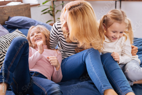 Smiling. Loving alert blond mother and her little daughters smiling and playing and while lying on the couch