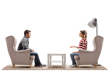 Young couple seated in armchairs having a conversation