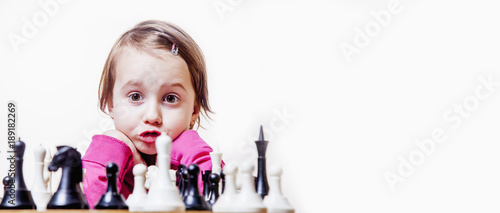 Future champions. Humorous photography. Beautiful child girl learns to play chess. (Development, childhood, success, wunderkind concept)