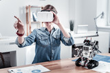 Virtual reality. Young woman raising hands and sitting at her workplace while looking forward - 189186864