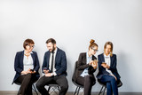 Business people using smart phones sitting in a row on the white wall background - 189197404