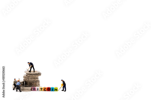 The image of the miniature figure of the workers are working around the coin stacks and isolated on white background with copy space. The image is for the concept of treasure mining or bitcoin mining.
