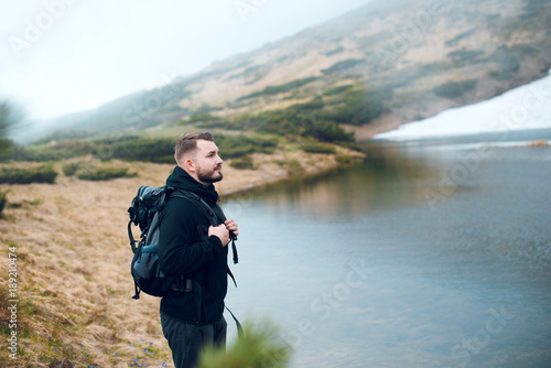 A man with a beard and a backpack stands and looks at a mountain lake