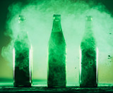 Three green bottles standing in a green dust. - 189210899
