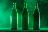 Three green beer bottles on a dusty background. - 189211015