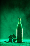 Beer bottle and a shamrock on a dusty background - 189211018