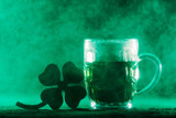 Beer mug with green beer and shamrock in a smoke. - 189211098
