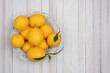 High angle shot of a basket of fresh picked lemons on white wood table. Horizontal format with copy space.