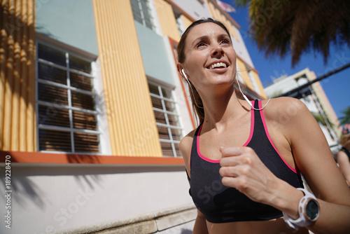 Plexiglas Fitness Jogger woman running in the street of sunny city