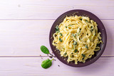 Tagliatelle pasta with spinach, garlic and Parmesan cheese on purple wooden background.