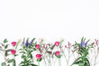 Flowers composition. Border made of various colorful flowers on white background. Flat lay, top view, copy space