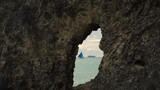 Sailing boat view through a hole in the rock. Sailing ship yachts with blue sails in the ocean. Sail boat on sea. Philippines, Boracay. Travel concept. - 189243493