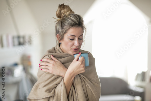 Foto Murales Beautiful middle-aged woman drinks tea from a glass in a cold living room dressed in a cotton becouse of cold winter. A sick girl drinks from a blue cup in the living room.