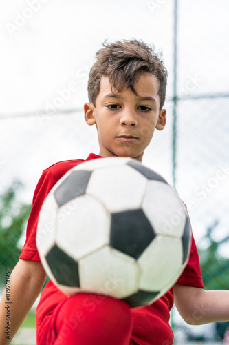 Fotobehang Voetbal Child soccer player juggling ball with his knee.
