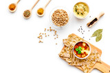 Middle Eastern cuisine. Bowl with hummus among pieces of crispbread and spices on white background top view copy space - 189276476