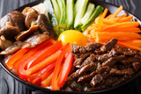 Delicious Bibimbap with beef, egg, vegetables, shiitake and rice close-up in a bowl on the table. horizontal - 189295026