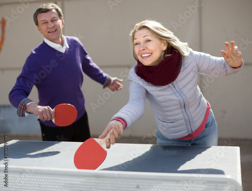 Happy mature man and a woman playing table tennis